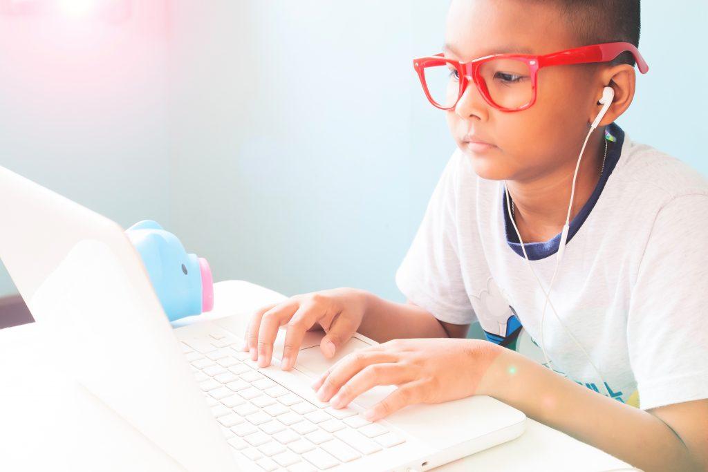 enfant portant des lunettes rouges et utilisant un ordinateur