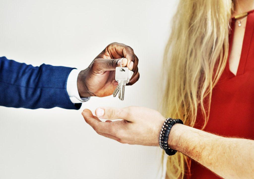 Un homme donne des clés à un couple