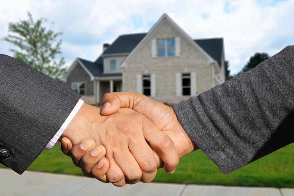 Mains serrées avec une maison en arrière-plan