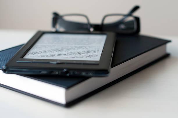 Liseuse électronique posée sur un livre papier avec une paire de lunettes de lecture