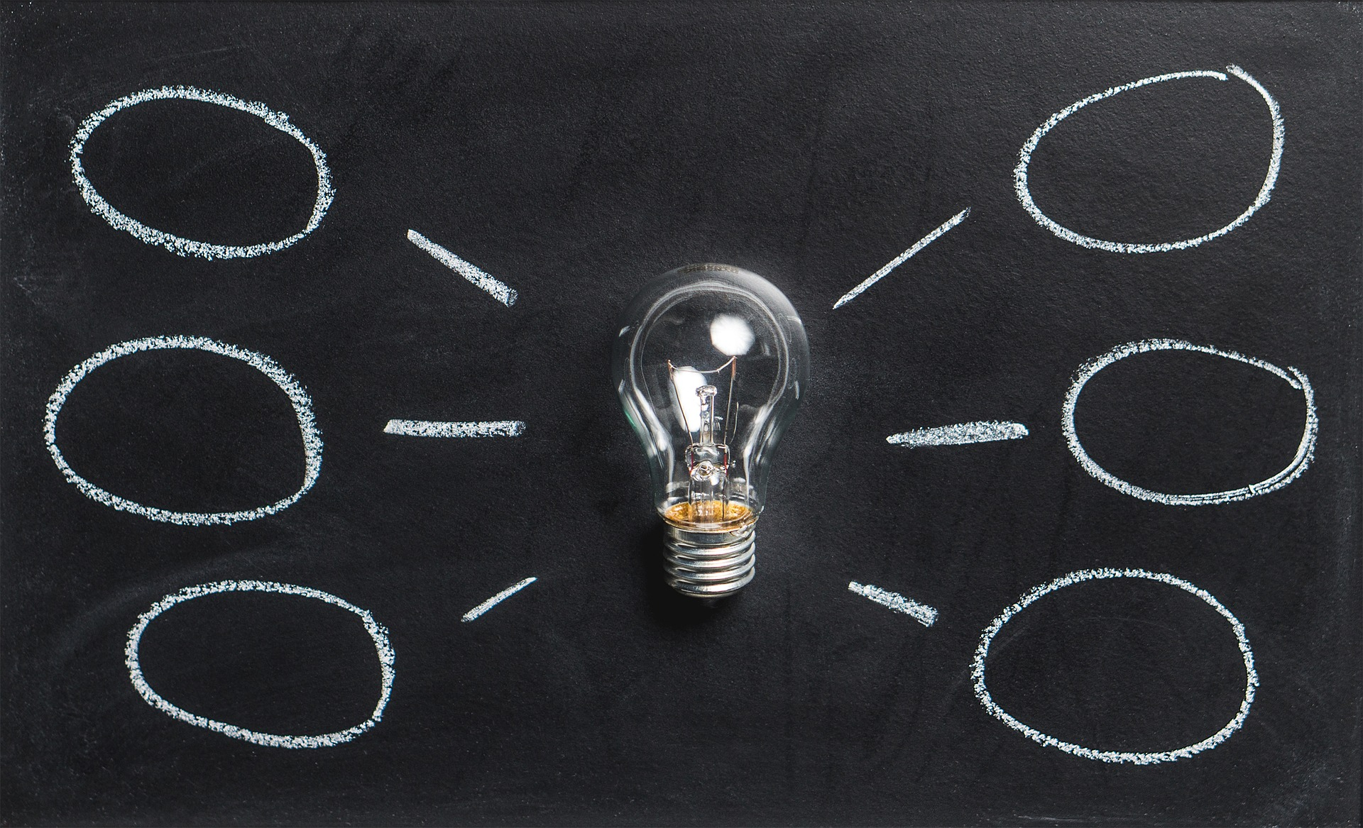 Ampoule posée sur un tableau noir entourée par des bulles dessinées à la craie blanche