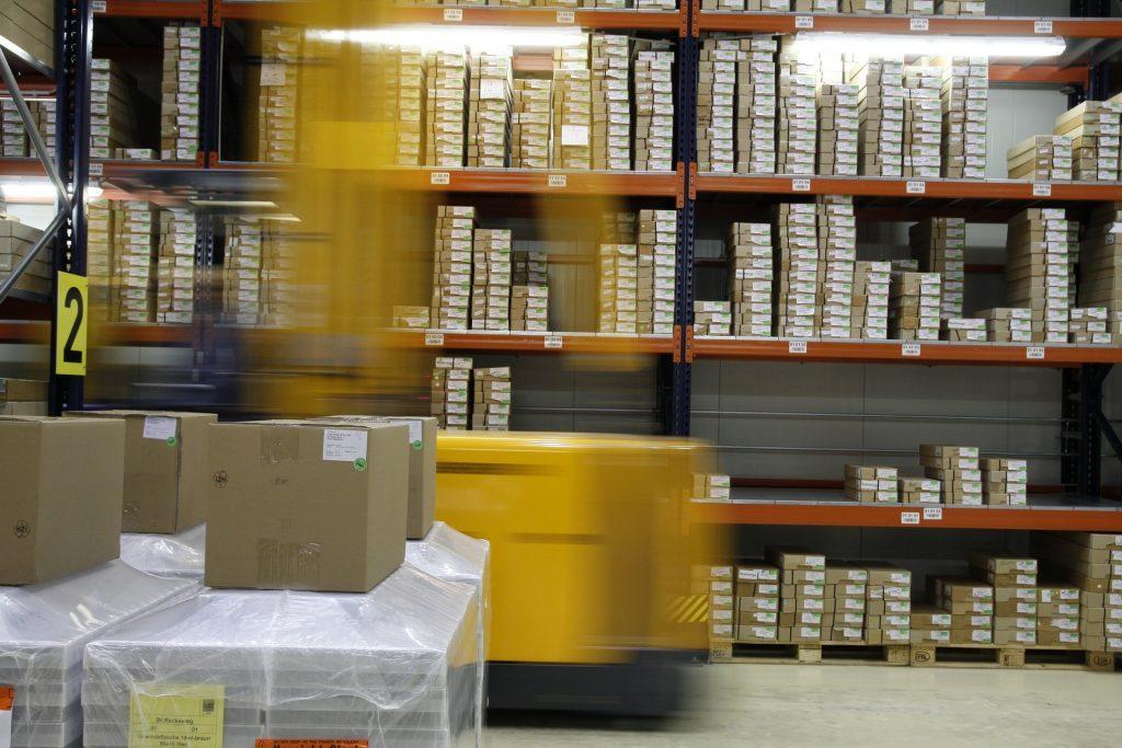 Entrepôt de stockage où des colis sont rangés sur de grandes étagères