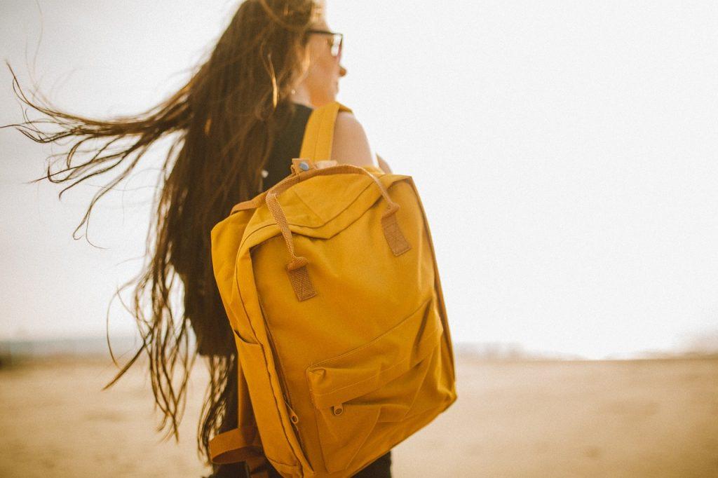 jeune fille portant un sac à dos jaune
